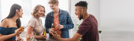 Photo for Panoramic concept of multiethnic friends with bottles of beer talking during party - Royalty Free Image