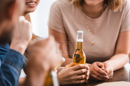Photo for Cropped view of woman holding bottle of beer near multicultural friends - Royalty Free Image