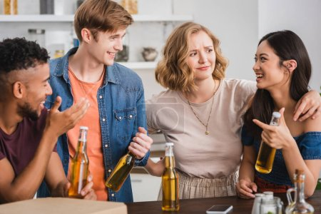 Photo for Excited multicultural friends with bottles of beer talking during party - Royalty Free Image