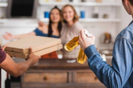 Photo pour Foyer sélectif des hommes tenant des boîtes de bière et de pizza près des femmes multiculturelles sur fond - image libre de droit