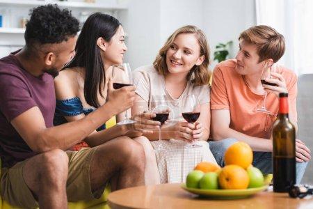 Photo pour Amis multiculturels parler tout en tenant des verres de vin rouge dans la cuisine - image libre de droit