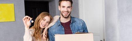 panoramic shot of joyful woman holding keys near boyfriend with carton box, moving concept