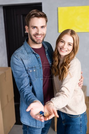 pleased man and woman holding keys in hands, moving concept