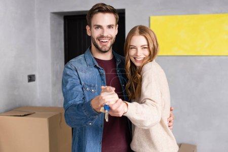 heureux homme et femme tenant les mains et les clés près de la boîte, concept mobile