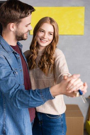 Photo pour Couple heureux tenant la main et les clés à la maison, concept mobile - image libre de droit