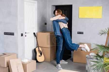 joyful woman hugging with boyfriend near carton boxes and acoustic guitar