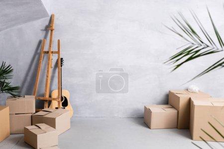 boîtes en carton près de chevalet, guitare acoustique et plantes