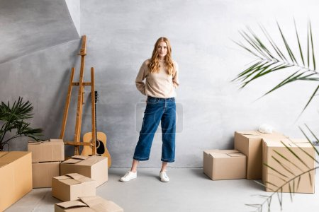 young woman standing near carton boxes and acoustic guitar, relocation concept