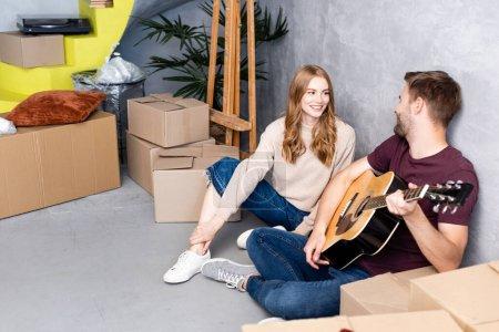 Photo pour Femme heureuse regardant son petit ami jouer de la guitare acoustique près des boîtes, concept de relocalisation - image libre de droit