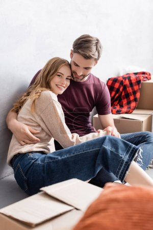 Photo for Pleased man sitting of floor and hugging girlfriend near boxes - Royalty Free Image