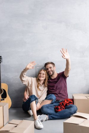 couple waving hands and sitting near acoustic guitar and boxes