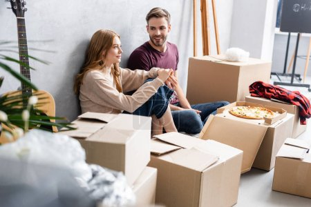 selective focus of man looking at girlfriend near carton boxes and pizza, moving concept