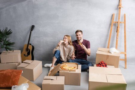 young woman eating pizza near man and carton boxes, relocation concept
