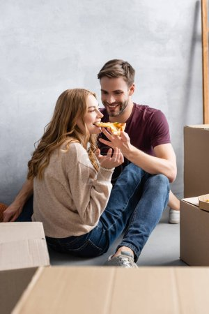 selective focus of joyful man feeding pleased girlfriend with pizza near carton boxes, moving concept