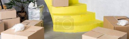 Photo pour Boîtes en carton sur les escaliers jaunes dans un nouvel appartement, concept de déménagement - image libre de droit