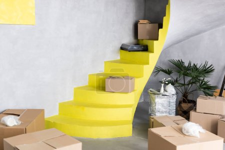 Photo for Carton boxes on yellow stairs in new apartment, moving concept - Royalty Free Image