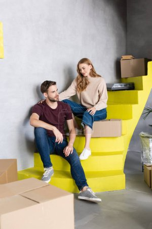 Photo for Woman touching boyfriend while sitting on stairs near boxes - Royalty Free Image