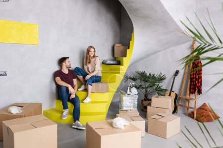 couple sitting on stairs near boxes, acoustic guitar and easel, relocation concept
