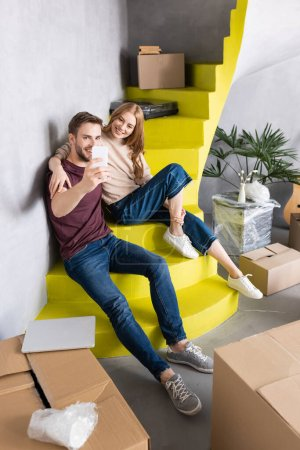 pleased couple sitting on yellow stairs and taking selfie near carton boxes