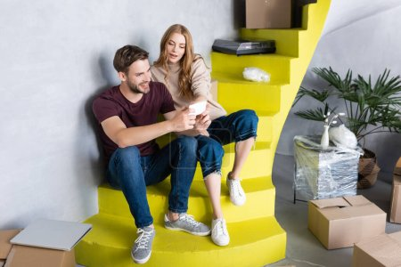 Photo for Couple sitting on stairs and looking at smartphone near boxes, relocation concept - Royalty Free Image