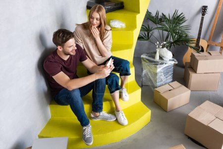 Photo for Man using smartphone while sitting on stairs with girlfriend and carton boxes - Royalty Free Image