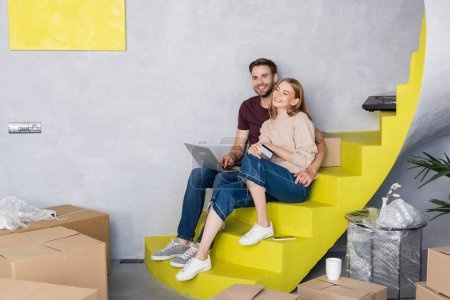 Photo for Man sitting on stairs near woman with credit card near laptop and boxes - Royalty Free Image