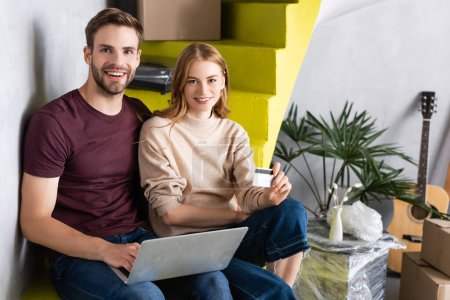 Photo pour Homme utilisant un ordinateur portable tout en étant assis sur les escaliers près de petite amie avec carte de crédit - image libre de droit