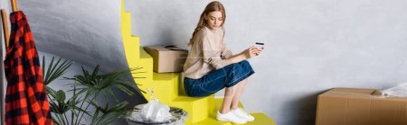 Photo for Horizontal image of young woman holding credit card and sitting on stairs near boxes - Royalty Free Image
