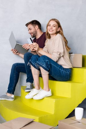 young woman holding credit card and sitting on stairs near man using laptop, relocation concept