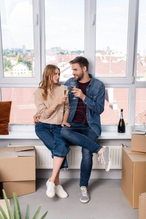 pleased man hugging woman and clinking glasses with champagne near carton boxes, moving concept