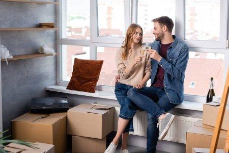 Mann umarmt Freundin und klappert Sektgläser neben Kartons, bewegendes Konzept