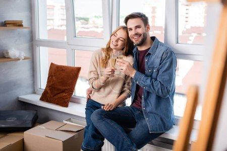 selektiver Fokus von zufriedenen Männern und Frauen, die Sektgläser neben Kartons klirren lassen, bewegendes Konzept