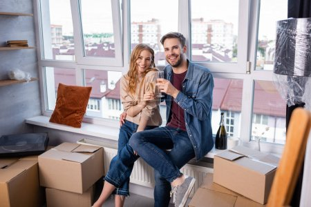 selective focus of pleased couple toasting glasses with champagne near carton boxes, moving concept