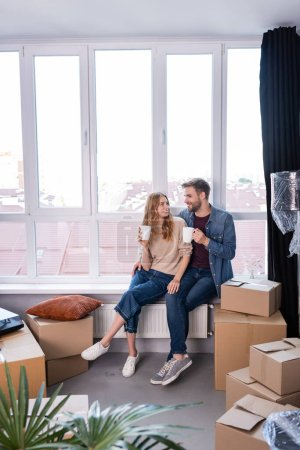 pleased couple holding cups with tea near carton boxes, moving concept