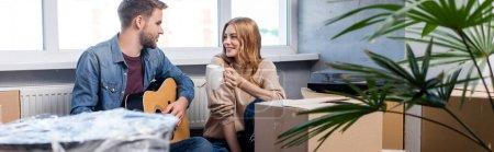 Photo pour Récolte panoramique de jeune homme jouant de la guitare acoustique près femme joyeuse avec tasse et boîtes en carton - image libre de droit