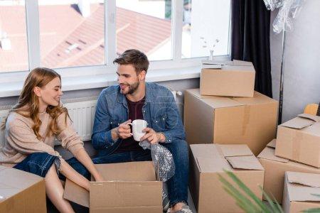 selektiver Fokus des Mannes mit Tasse und Auspacken der Schachtel mit Freundin, bewegendes Konzept