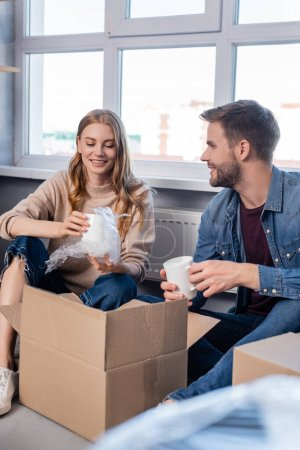selective focus of woman holding cup and unpacking box with boyfriend, moving concept