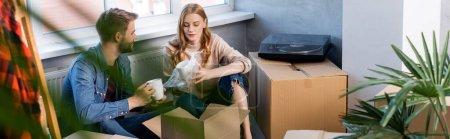foyer sélectif de femme joyeuse tenant tasse tout en déballant la boîte avec petit ami, plan panoramique