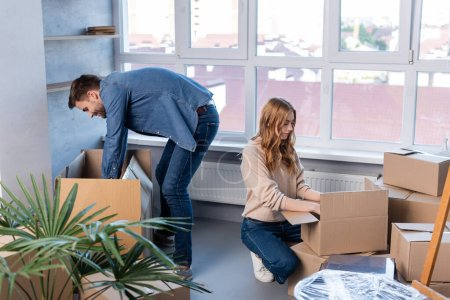 man and woman unpacking carton boxes in new home, moving concept