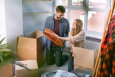 selektywne skupienie uwagi mężczyzn i kobiet dotykających poduszek rozpakowujących pudełka kartonowe w nowym domu, przenosząc koncepcję