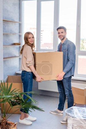joyful man and woman holding carton box and looking at camera, moving concept