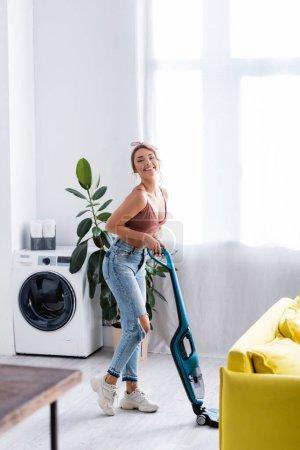 Photo pour Femme au foyer moderne avec aspirateur regardant la caméra près de l'usine et de la machine à laver - image libre de droit
