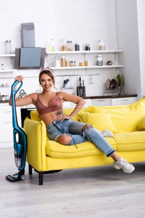 Photo for Housewife with hand on hip sitting on couch and holding vacuum cleaner at home - Royalty Free Image