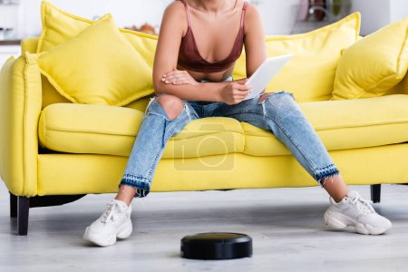 Cropped view of woman with digital tablet and robotic vacuum cleaner