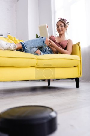 Selective focus of woman lying on couch and robotic vacuum cleaner