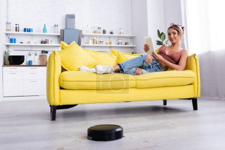 Woman lying on couch with digital tablet and robotic vacuum cleaner on floor