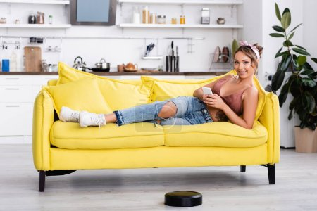 Photo for Selective focus of housewife using smartphone while lying on couch near robotic vacuum cleaner - Royalty Free Image