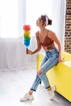 Photo pour Femme au foyer moderne soufflant sur la brosse à poussière près du canapé jaune à la maison - image libre de droit
