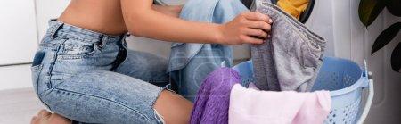Photo pour Vue panoramique de la femme au foyer en jeans tenant des vêtements près du panier à linge à la maison - image libre de droit