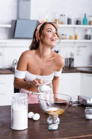 Selektive Zugabe von Zucker in Schüssel mit Eiern in der Nähe von Mehl und Mixer auf dem Küchentisch